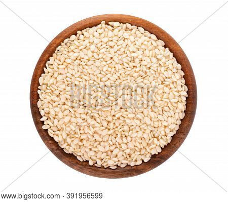 Sesame Seeds In Wooden Bowl, Isolated On White Background. Organic Dry Sesame Seeds. Top View.