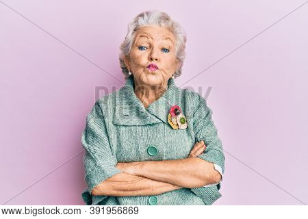 Senior grey-haired woman wearing casual clothes looking at the camera blowing a kiss being lovely and sexy. love expression.