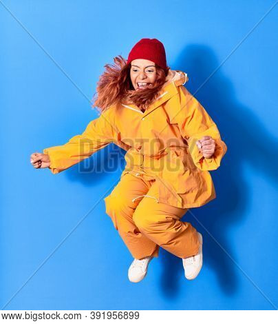 Young beautiful latin woman wearing fisher raincoat smiling happy. Jumping with smile on face celebrating with fists up over isolated blue background