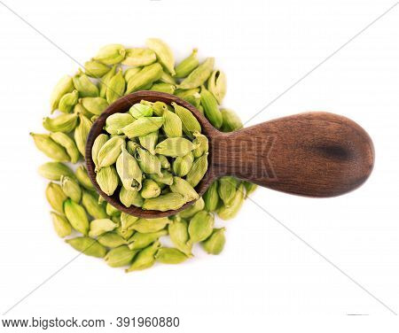Cardamom Seeds In Wooden Spoon, Isolated On White Background. Pile Of Green Cardamom Pods. Top View.