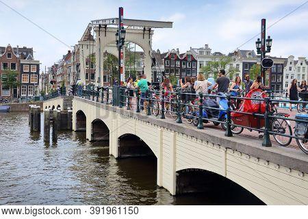 Amsterdam, Netherlands - July 8, 2017: People Visit Magere Brug (the Skinny Bridge) In Amsterdam, Ne