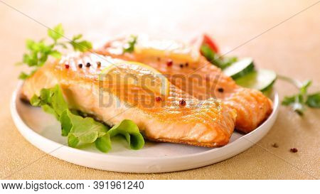 salmon fillet and lettuce in plate