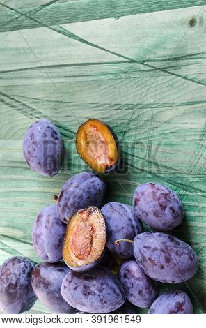 Plum And Dried Plum On Green Wooden Background Top View Prunes