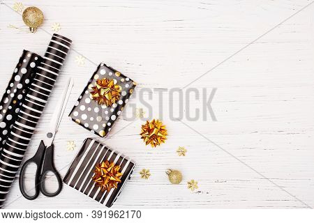 Christmas Background With Gift Boxes, Paper Rolls And Decorations On White Wooden Background. Prepar