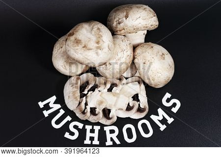 A Bunch Of White Champignons. Some Of Them Are Cut Into Slices. The Inscription At The Bottom Of Mus
