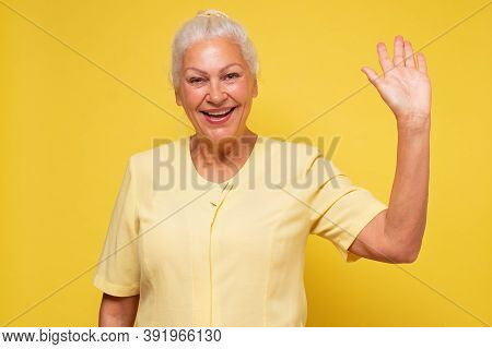 Portrait Of A Senior Hispanic Woman Smiling And Saying Hello At You Over Yellow Background.