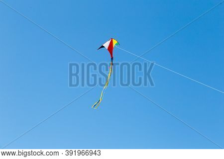Kite On The Blue Sky In Sunny Weather And Wind. Kite Flying In Summer With Copy Space. Liberty.