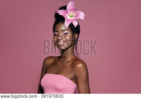 Pink Lily Hair Style. Young Beautiful African American Model With Bunned Hair Smiling And Posing Aga
