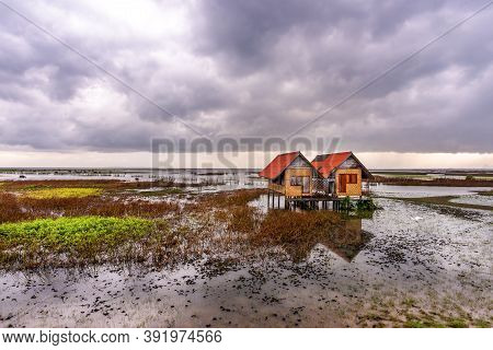 View Of An Abandoned House In The Middle Of The Lake With Sky And Cloud Rain In Sunset