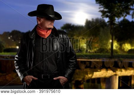 Stylish Young Man In A Cowboy Hat And Black Cloak On A Blurred Night Background With Evening Lights.