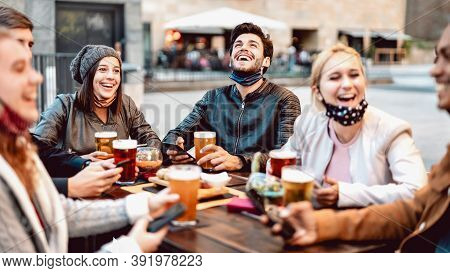 Young Friends Drinking Beer Wearing Face Mask - New Normal Lifestyle Concept With People Having Fun