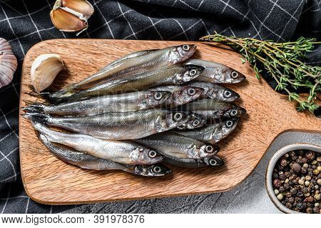 Raw Fresh Capelin Fish On Cutting Board. Gray Background. Top View