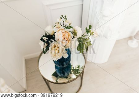 Vase Of Flowers On A Mirror Table In A White Bright Living Room. Cozy Home. High Quality Photo