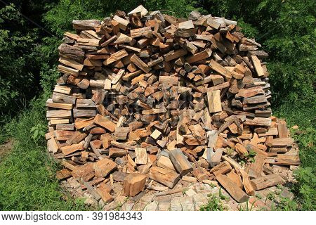 Heap Or Island Of Firewood. Alternative And Cheap Energy Source For Heating. Heating Season. Wooden
