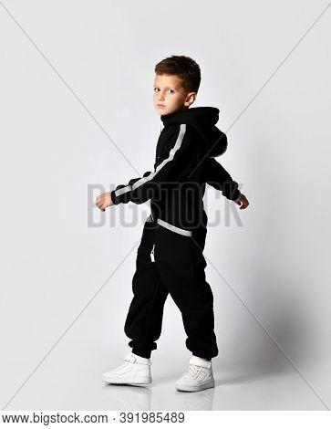 Handsome Boy In Black Warm Jumpsuit In Full Growth Motion Studio. The Schoolboy Turns Around, Showin