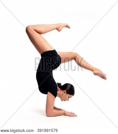 A Young Beautiful Female Gymnast In Sportswear Performs A Handstand. Training, Element Of Gymnastics