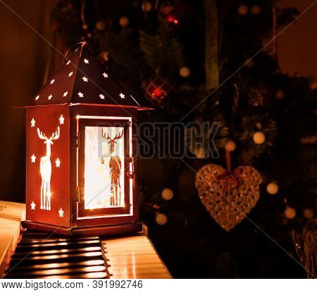Christmas Lantern On The Piano Keys On The Background Of The Christmas Tree In The Evening. Christma