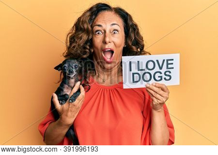Middle age hispanic woman holding chihuahua dog and paper with i love dogs phrase afraid and shocked with surprise and amazed expression, fear and excited face.