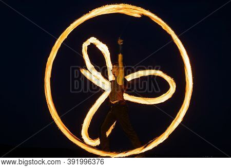 Having Tricks For Celebration. Man Perform Fire Tricks In Darkness. Fire Performance. Poi Twirling.