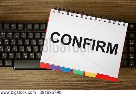 The Word Confirm Is Written On The White Notebook That Is On The Keyboard.