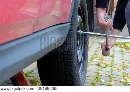A Wrench In The Hands Of An Auto Mechanic Unscrews The Bolts And Nuts Of A Car Wheel. Seasonal Repla