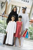 Family standing in mall smiling (selective focus) poster