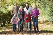 Family walking outdoors in park smiling poster