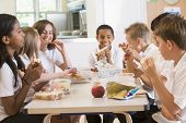 Students sitting at cafeteria table eating lunch (depth of field) poster