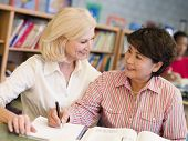Two women sitting in library with a book and notepad (selective focus) poster