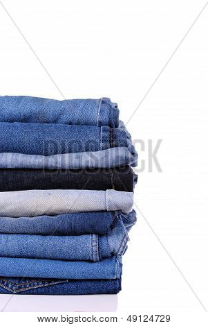 stack of different kind of blue jeans on white background