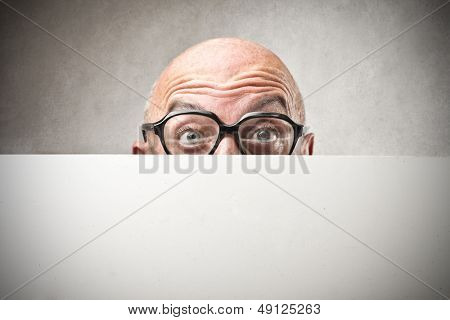 bald businessman hiding behind billboard