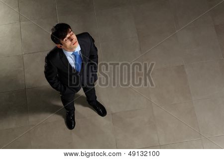 Image of young businessman with his eyes closed looking above. Top view