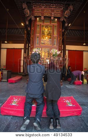 Two People Praying In A Temple In Shanghai