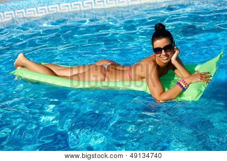 Beautiful woman laying on airbed in swimming pool at summertime, smiling.