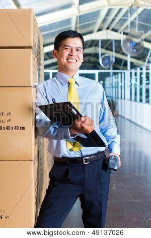 Young Indonesian man in a suit with a bar code scanner in a Asian warehouse of forwarding or logistics company