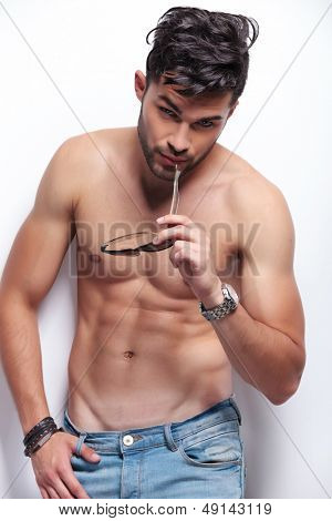young topless man bitting his sunglasses while looking at the camera. on light gray background