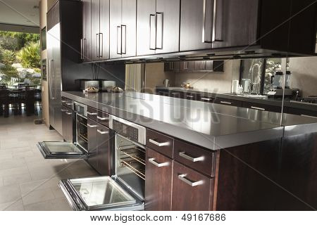 Interior of commercial kitchen with open oven and cabinets