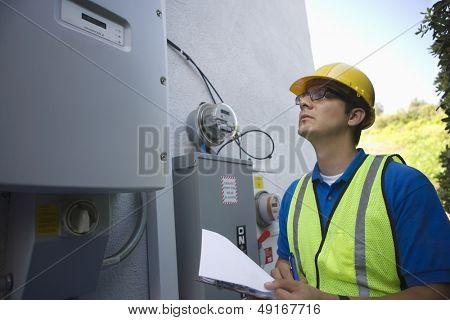 Maintenance worker reading meter of solar generation unit in Los Angeles; California