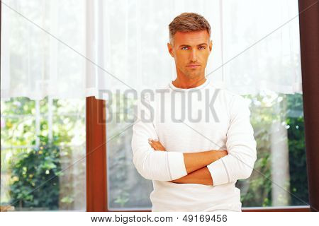 Handsome serios young man looking at camera poster