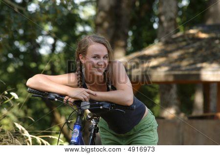 Teen Girl Resting On Handlebars Of Bicycle