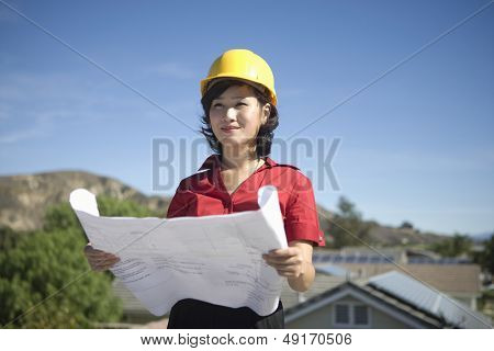 Confident young female solar panel worker holding blue print while looking away