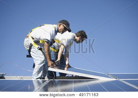 Side view of multiethnic engineers placing solar panel against blue sky