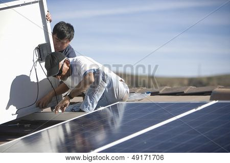Male workers fixing solar panel on roof top against sky