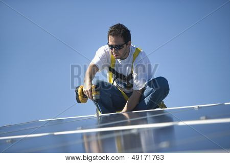 Young engineer drilling solar panel while crouching against clear blue sky