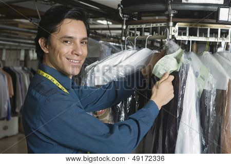Portrait of young male owner checking clothes tag in laundry