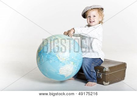 Beaming with smile toddler is holding the world