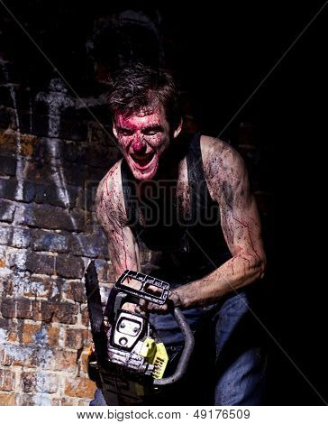 horrific madman on a dark background and gasoline-powered saw