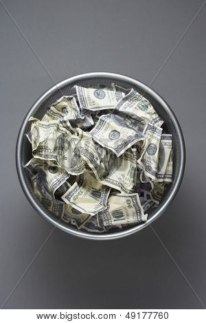 Dollar bills in wastebasket view from above