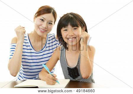 Girl studying with mother
