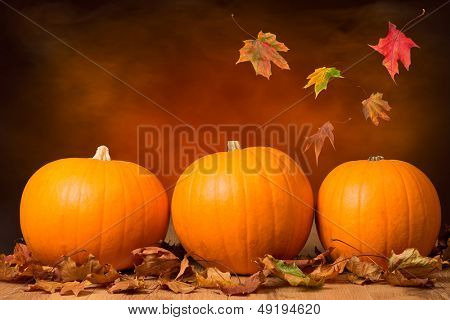Three pumpkins with fall leaves with seasonal background poster